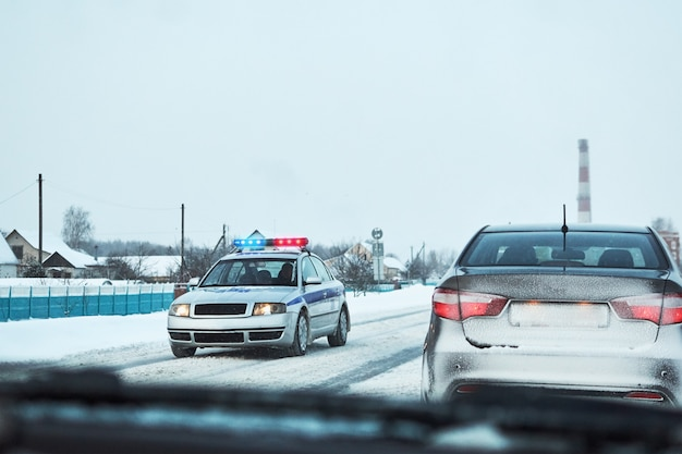 Polizeiwagen mit den roten und blauen blitzlichtern stoppte auto auf schneebedeckter straße des winters