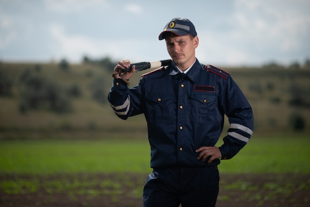 Polizist in uniform mit einem stab in der hand