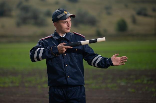 Polizist in uniform mit einer stange in seiner hand auf dem hintergrund der ländlichen landschaft