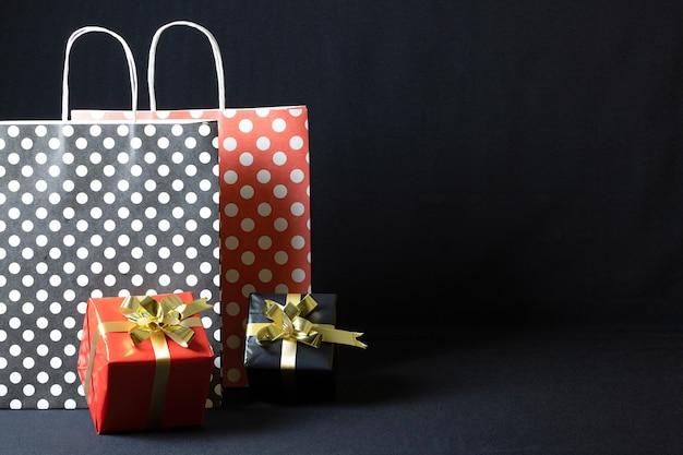 Polka dots papiertüten mit weihnachtsgeschenkboxen lokalisiert auf einem dunklen hintergrund