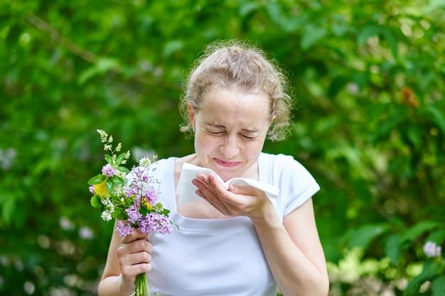 Pollenallergie, mädchen, das mit blumenstrauß von blumen niest. konzept: saisonale allergie.