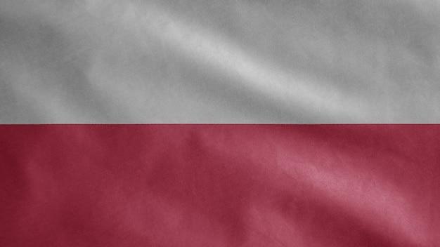 Polnische flagge weht im wind. nahaufnahme von polen schablonenblasen, weiche und glatte seide. stoff stoff textur fähnrich hintergrund