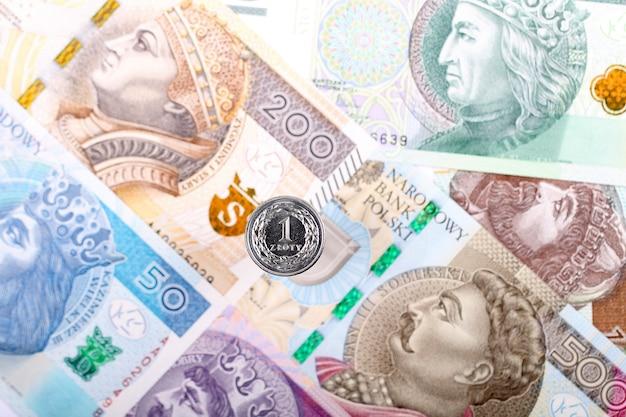 Polnische zloty-münze auf dem hintergrund von polnischen banknoten