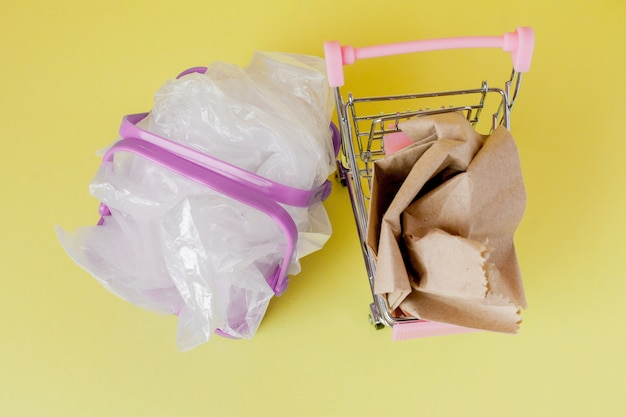 Polyethylen- und papiertüten in einem einkaufskorb auf gelbem grund