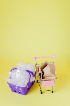 Polythen und papiertüten in einem einkaufskorb auf einem gelben hintergrund