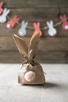 Pom pom osterhasen handwerk. papierhintergrund des osterhasendekorationspapierschnittes. diy feiertagsgirlande der bunten kaninchen