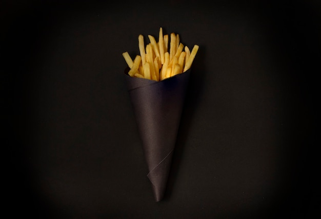 Pommes auf einem schwarzen tisch, in einer schwarzen packung, horizontal