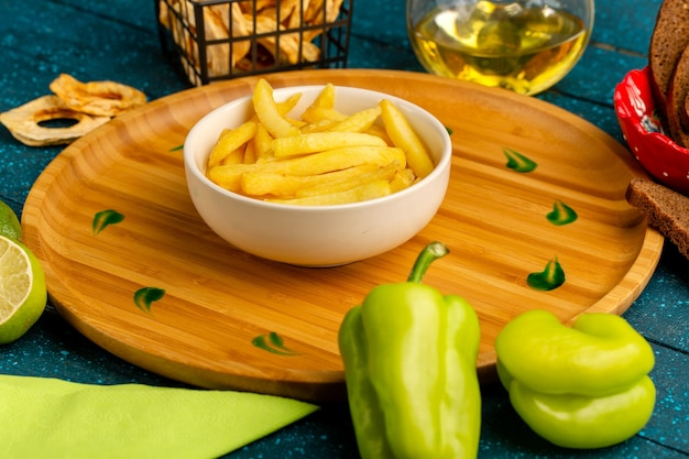 Pommes frites auf dem teller zusammen mit grünem paprikaöl auf blau