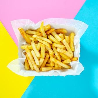Pommes-frites auf einem bunten hintergrund