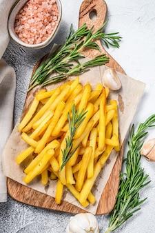Pommes frites auf einem schneidebrett, bratkartoffeln. weißer hintergrund. draufsicht.