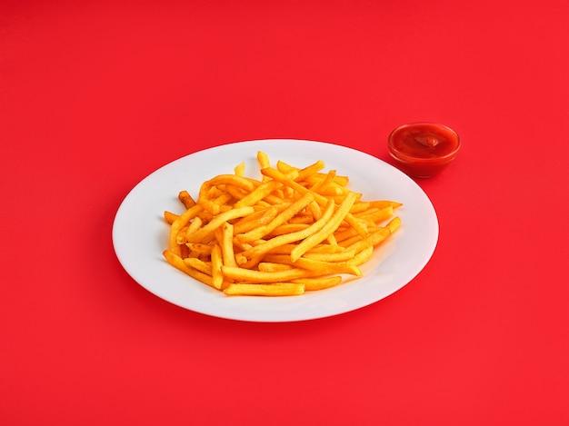 Pommes-frites auf einer platte auf rot