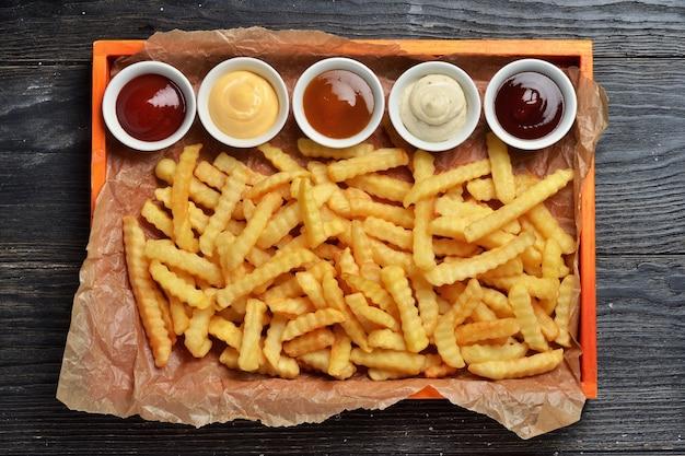 Pommes frites auf großem holztablett mit saucen auf schwarzem holzhintergrund