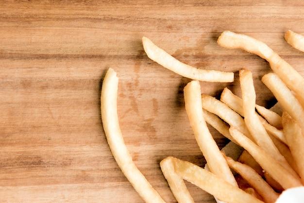 Pommes-frites auf hölzernem hintergrund.