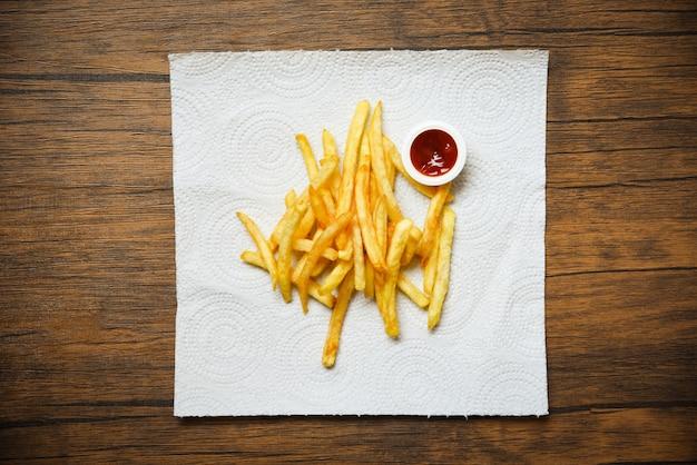 Pommes-frites auf weißbuch mit ketschup auf hölzernem