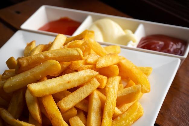 Pommes frites auf weissem teller serviert mit chili, tomatensauce und mayonnaise.