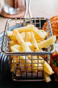 Pommes-frites dienten im stahlkorb für das essen mit burger.