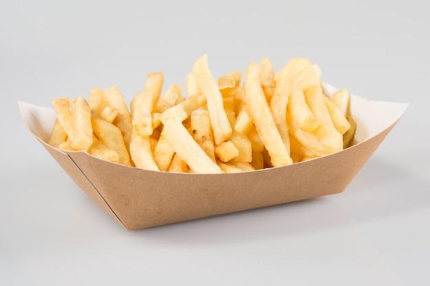 Pommes frites im karton in kraft blankopapier fry box auf weißem hintergrund isoliert