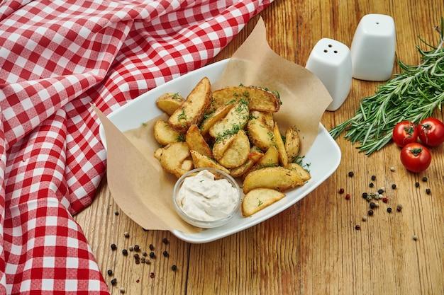 Pommes frites in bastelpapier auf grauer platte auf holz. amerikanisches traditionelles fast food.