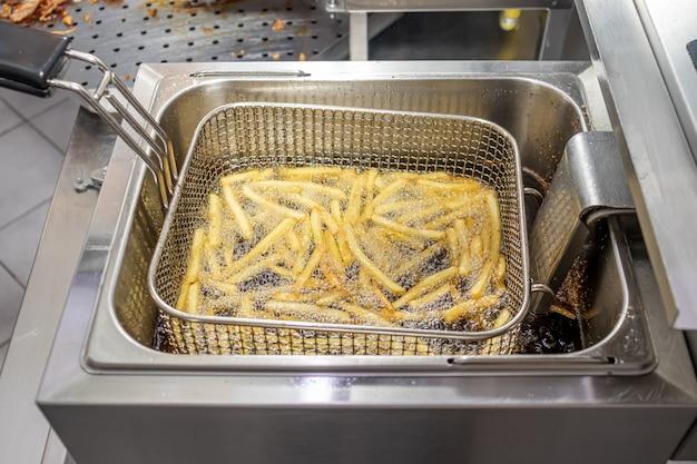 Pommes frites in der friteuse in heißem öl in einem lokalen restaurant braten
