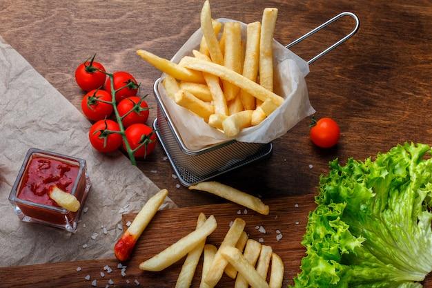 Pommes-frites in einem gitter mit ketchup-, salat- und kirschtomaten auf hölzerner brauner tabelle