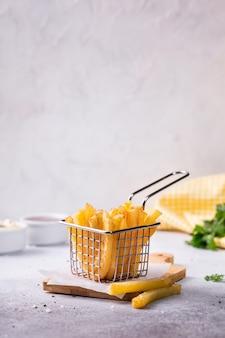 Pommes-frites in einem korb auf beton