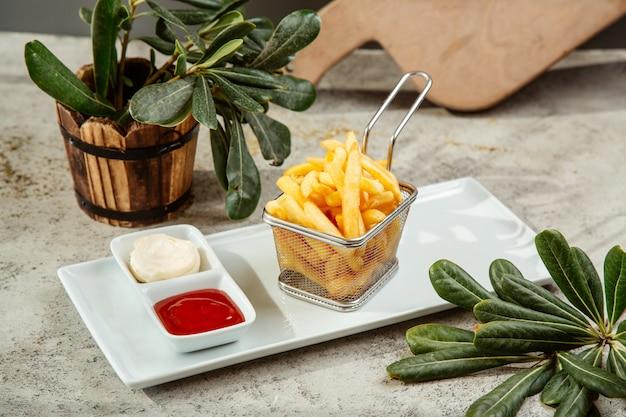 Pommes frites in einem korb serviert mit ketchup und mayonnaise