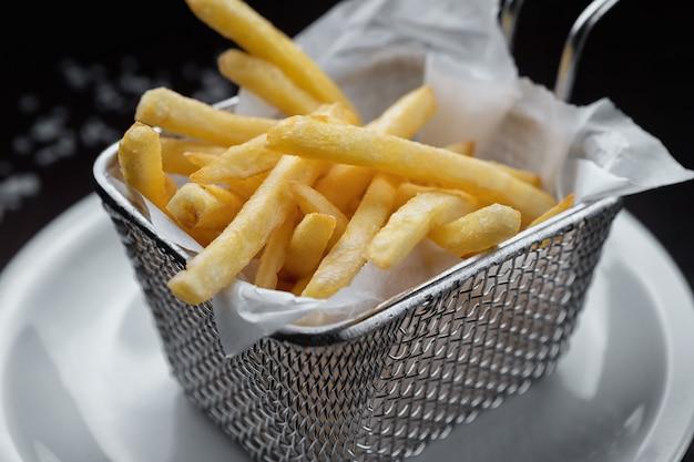 Pommes frites in einem metallgitter, auf einem weißen teller