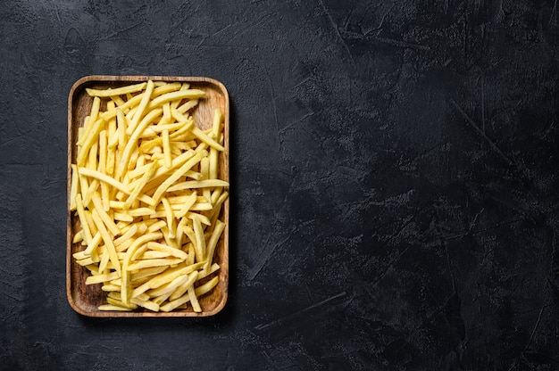 Pommes frites in einer holzschale. bio-kartoffeln. schwarzer hintergrund. draufsicht.