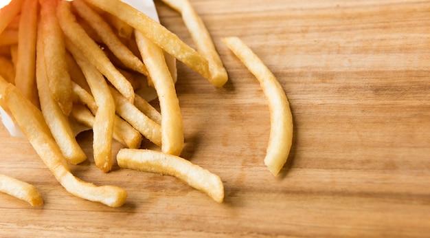 Pommes frites in einer kleinen weißen papiertüte auf holzbrett