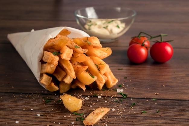 Pommes frites, in einer papiertüte auf holz