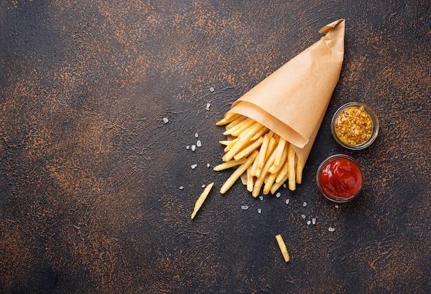 Pommes frites in einer papiertüte mit saucen