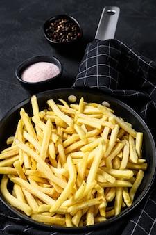 Pommes frites in einer pfanne. schwarzer hintergrund. draufsicht
