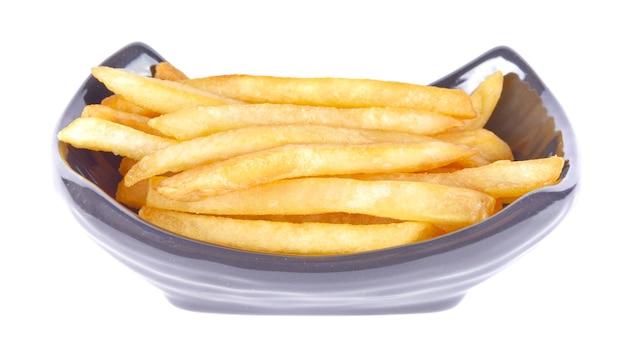 Pommes frites in einer schwarzen schüssel auf einer weißen oberfläche