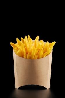 Pommes frites in kraft pommes frites box auf schwarzem hintergrund mit kopienraum