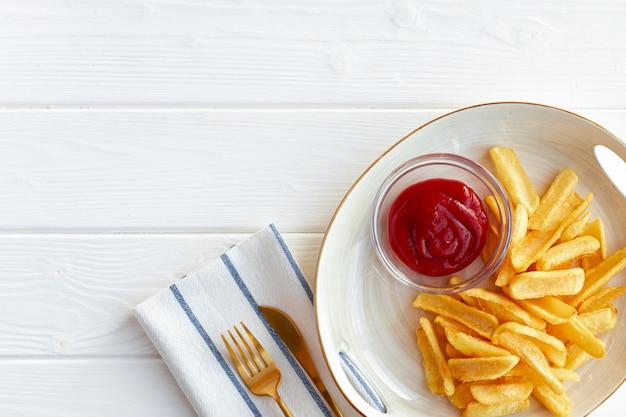 Pommes frites kartoffeln in teller mit sauce auf holztisch nahaufnahme