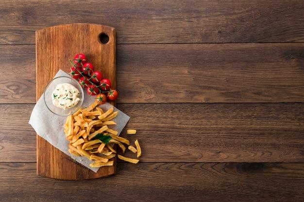 Pommes frites, kirschtomaten, knoblauchsauce auf holz