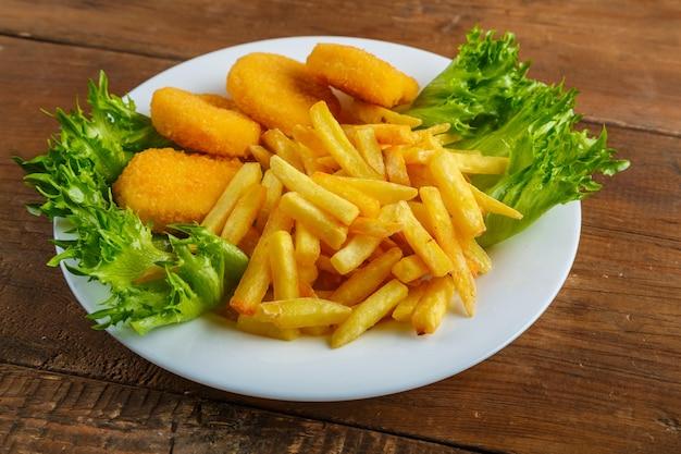 Pommes frites mit chicken nuggets in einem teller mit salat auf einem holztisch