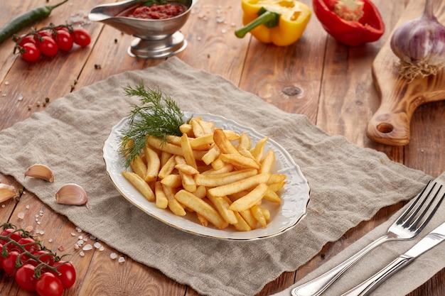Pommes frites mit dill, hölzernem hintergrund