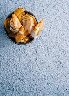 Pommes frites mit gewürzen und soße in einer metallschale auf blauem tischhintergrund