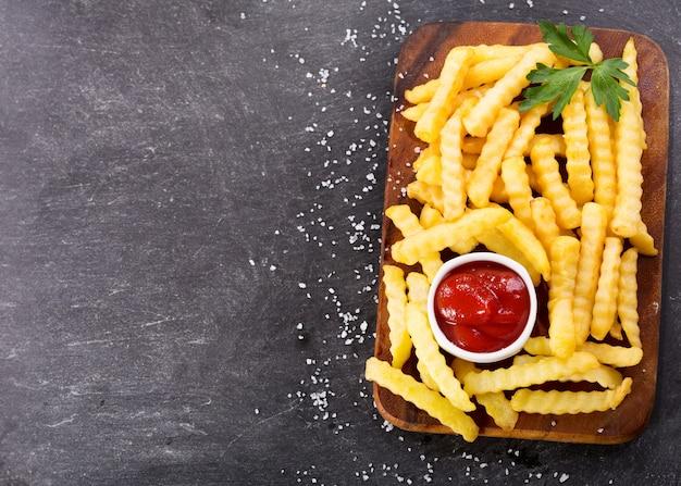 Pommes frites mit ketchup auf dunklem hintergrund