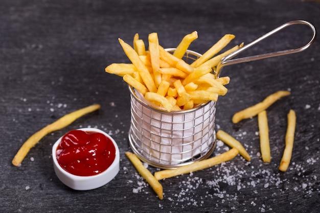 Pommes frites mit ketchup auf dunklem tisch