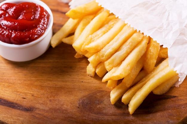 Pommes frites mit ketchup auf holzbrett
