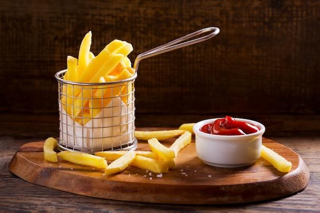 Pommes frites mit ketchup auf holztisch