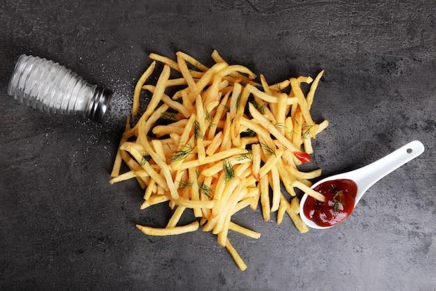 Pommes frites mit ketchup, salz und dill auf dem tisch