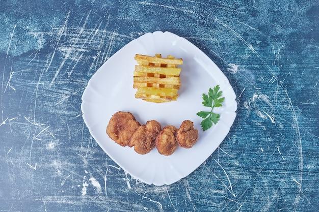 Pommes frites mit knusprigen nuggets.