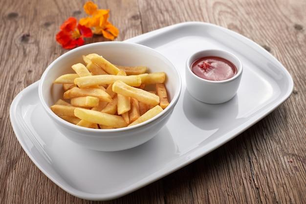 Pommes frites mit sauce auf einem weißen teller
