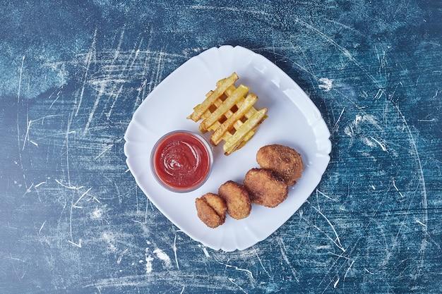 Pommes frites mit saucen und nuggets.