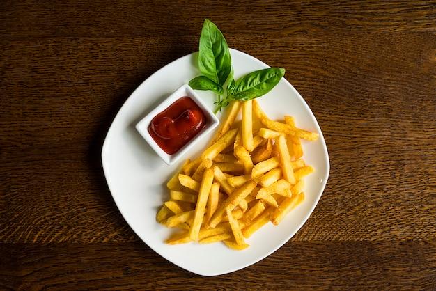 Pommes-frites mit soße auf einer weißen platte