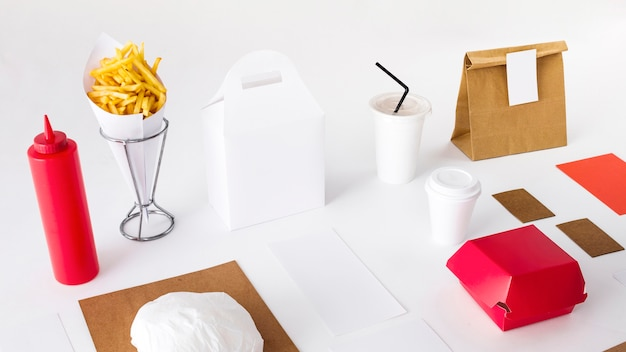 Pommes frites mit verpackten lebensmitteln; soße flasche und entsorgung tasse auf weißem hintergrund