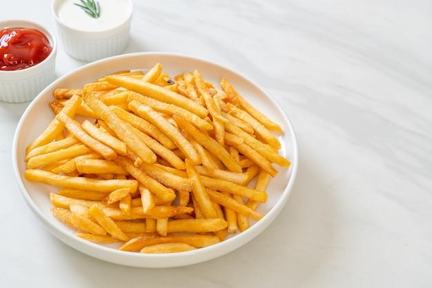 Pommes frites oder kartoffelchips mit sour cream und ketchup